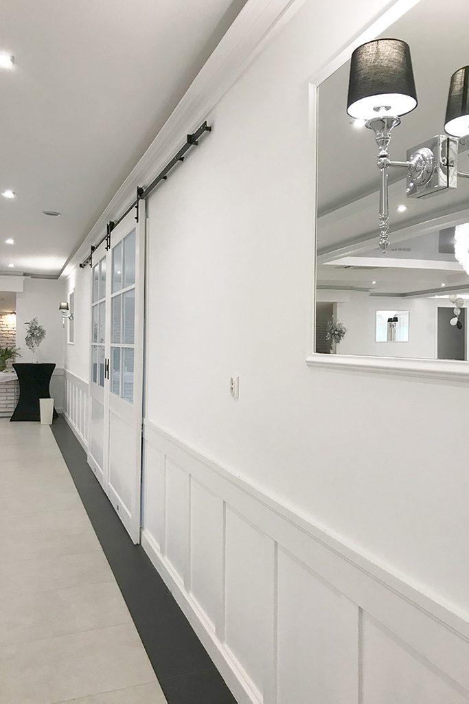weiße Schiebetüren, Große Schiebetüren, Doppelschiebetür, Schiebetüren mit Glas, weiße Holztüren mit Glas, Eingang zum Ballsaal, Spiegel in einem weißen Rahmen
