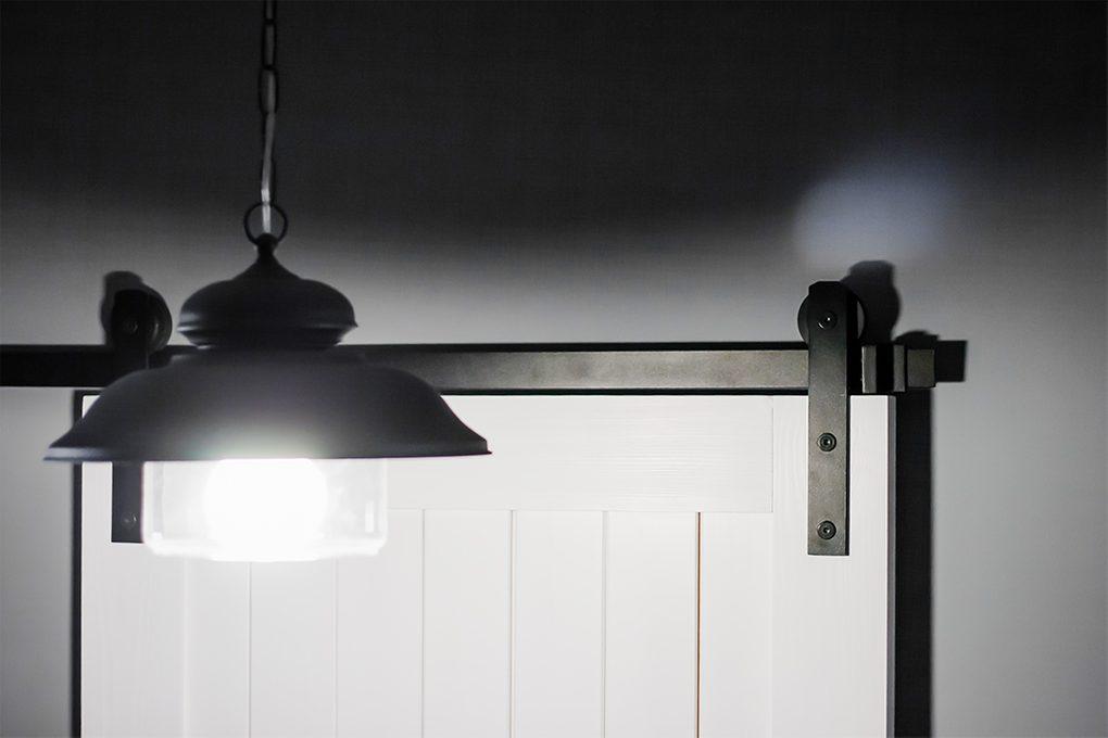 Schiebesystem, weiße Schiebetür, graue Wände in der Halle, schwarze Hängelampe in der Halle, Dekenlampe Schwarz Metall