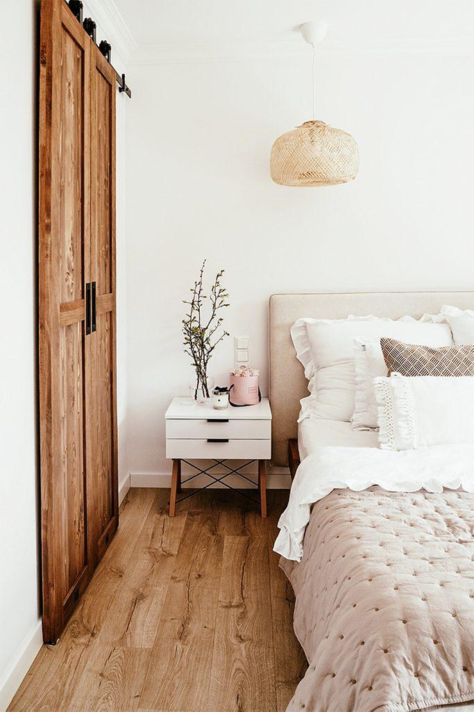 Kleiderschrank im Schlafzimmer, Schiebetür zum Kleiderschrank, weiß und Holz, natural beige, dekorative Kissen, weißer Nachttisch