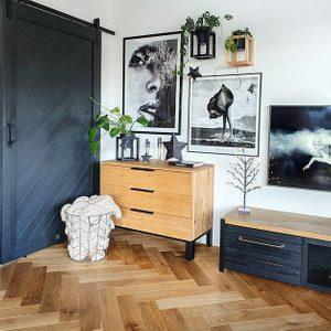 Collage mit Grafiken an der Wand, schwarzen Schiebetüren, Holzschrank mit Metallbeinen
