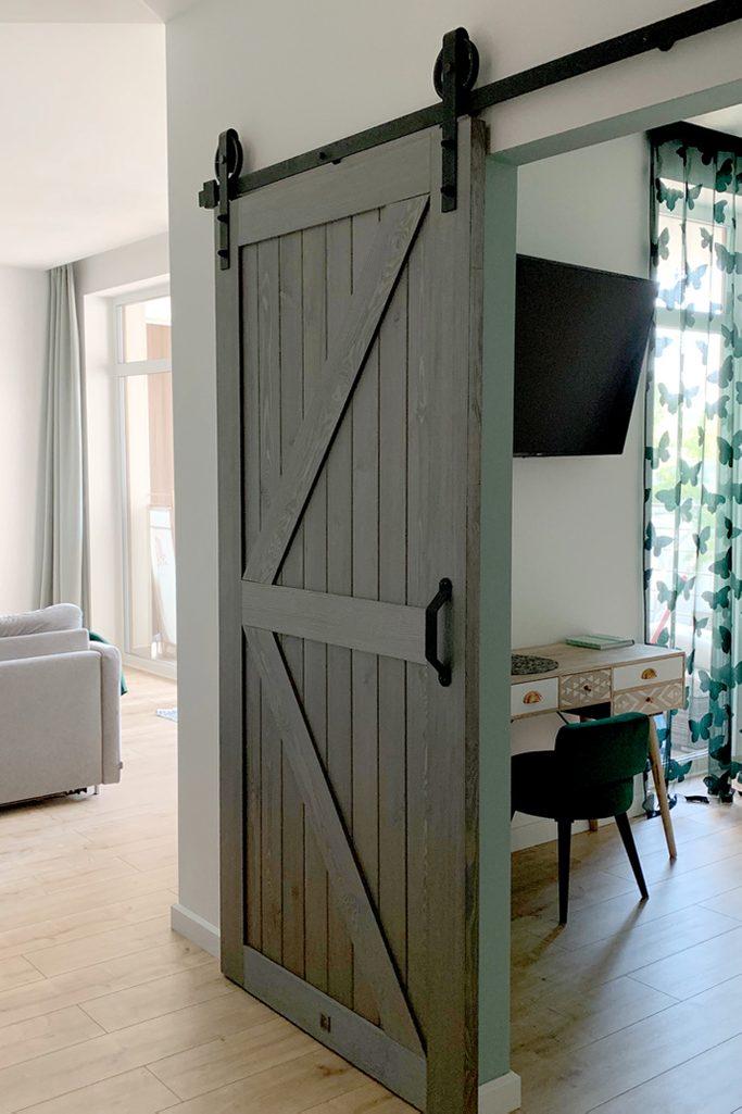 Holzschiebetüren, Scheunen-Schiebetüren, Schiebetür holz grau, goldene Accessoires im Innenraum, modernes Interieur, Schlafzimmerschiebetür
