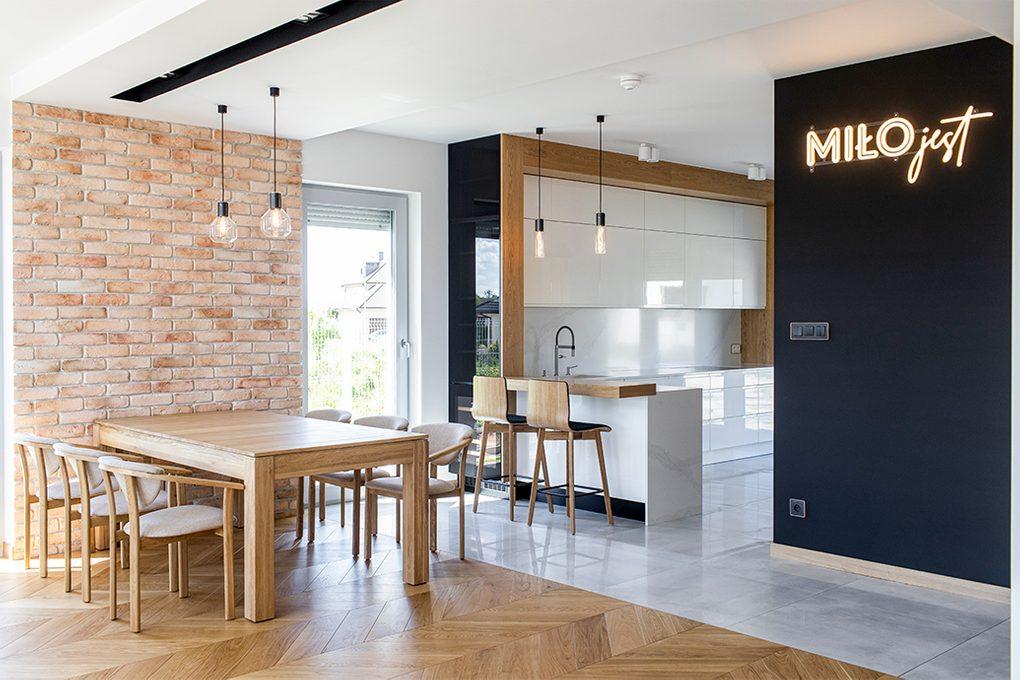 Essecke in der Küche, große offene Küche, Industrielampen in der Küche, Leuchtreklame, weiße Möbel in der Küche, hochglänzende Küchenmöbel