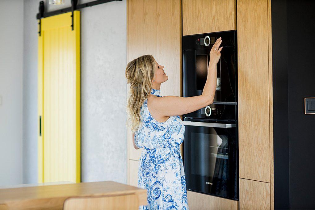 moderne Küche, gelbe Schiebetüren, Schiebetüren in der Küche, große Küche, Küchenmöbel, Holzelemente in der Küche. Küche mit Speisekammer