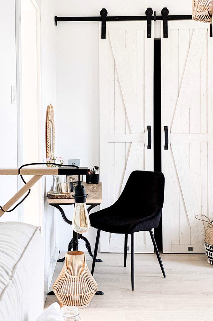 Schlafzimmer mit Kleiderschrank, Schlafzimmer im rustikalen Stil, schmale Schiebetür, Schiebetür im Kleiderschrank, weiße Tür, rustikales Weiß, schwarze Schlafzimmerdekorationen