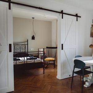 moderner Retro-Stil, Mietwohnungen Wroclaw, Doppelschiebetüren, weiße Schiebetüren, barn door, offener Raum, Doppeltür für Schlafzimmer, Retroschlafzimmer, Schaukelstuhl im Schlafzimmer