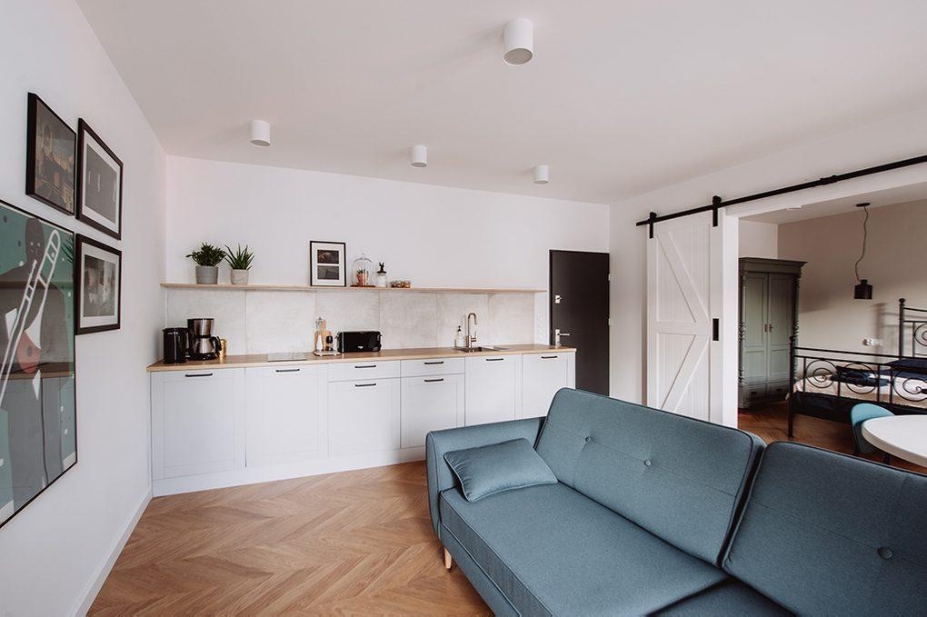 moderner Retro-Stil, Mietwohnungen Wroclaw, Doppelschiebetüren, weiße Schiebetüren, Wohnung mit Küchenzeile, offener Raum, Küchenzeile in Weiß