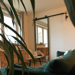 Schiebetür mit Spiegel, Tür mit Spiegel in einem Metallrahmen, Schiebetür in einem modernen Interieur, grüne Sofa, große Spiegel im Wohnzimmer