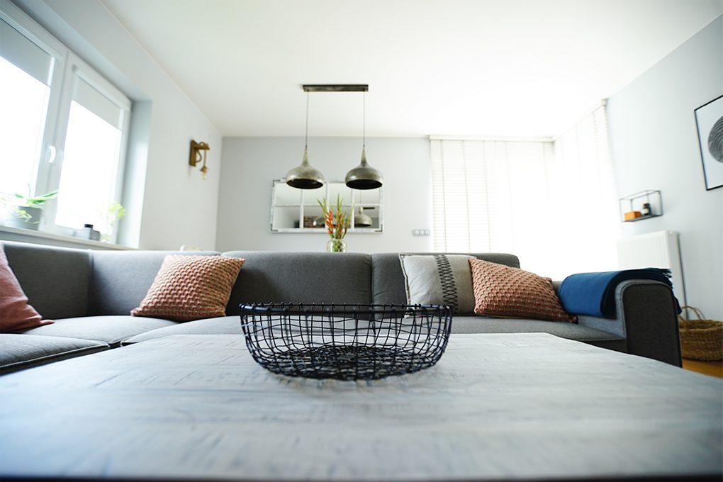 graues Sofa im Wohnzimmer, hängende Metall Lampen, bunte Kissen