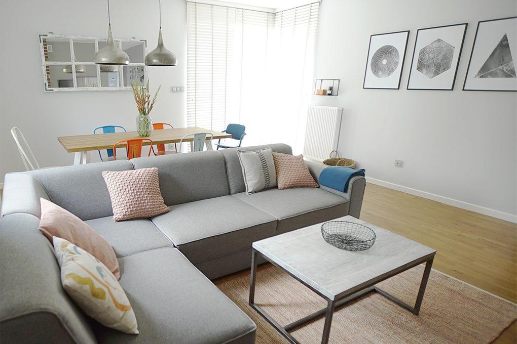 Wohnzimmer Anordnung, graues Sofa im Wohnzimmer, bunte Accessoires im Wohnzimmer, Wanddekorationen