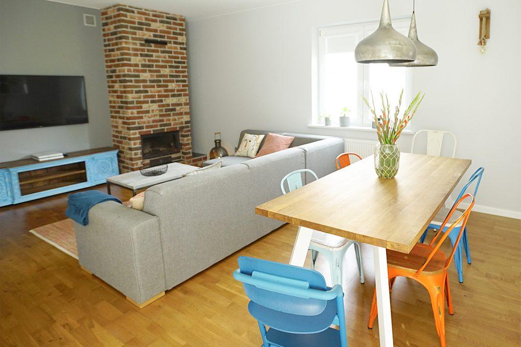 Anordnung des Wohnzimmers, gemauerter Kamin, Kamin Wohnzimmer, graues Sofa im Wohnzimmer, bunte Accessoires, Essecke im Wohnzimmer