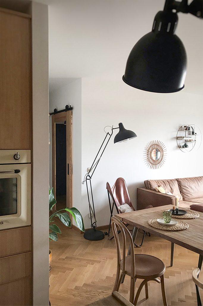 Schiebetür zum Büro, Holztür mit Spiegel, Schiebetür mit Spiegel, große Stehlampe aus Metall, Ledersessel auf Metallbasis, Vintage-Sessel, Parkettboden im Wohnzimmer, Spiegel im Flur, Retro-Stühle