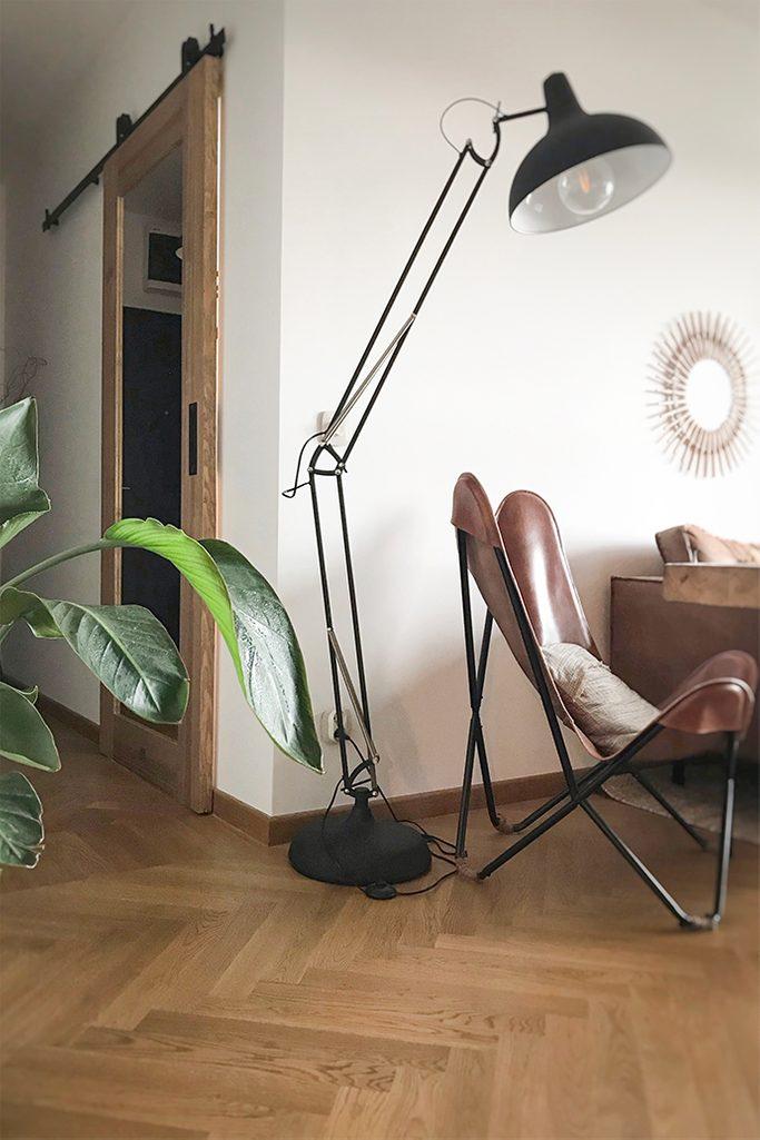 Schiebetür zum Büro, Holztür mit Spiegel, Schiebetür mit Spiegel, große Stehlampe aus Metall, Ledersessel auf Metallbasis, Vintage-Sessel, Parkettboden im Wohnzimmer, Spiegel im Flur