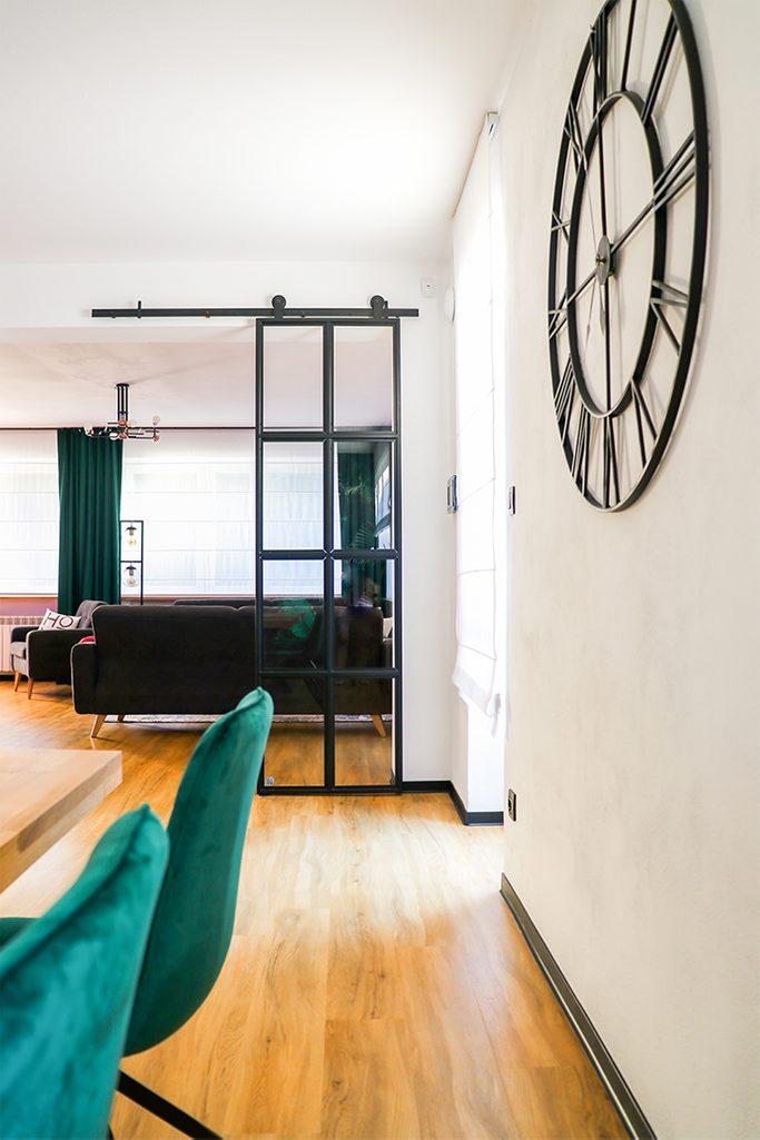 schwarze Metallwanduhr, Uhr im Industriestil, Loftdekor, Metalltür mit Glas, Lofttür, Metallglasschiebetür, schwarze Glastür, grüne Esszimmerstühle, zum Esszimmer offenes Wohnzimmer, grüne Vorhänge