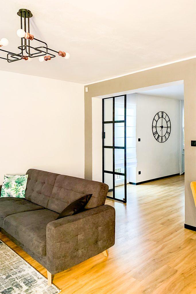 Loft-Innenraum, Glastür in einem Metallrahmen, Glasschiebetür, Industrielampe im Wohnzimmer, graues Sofa, offenes Wohnzimmer, industrielle Wanduhr