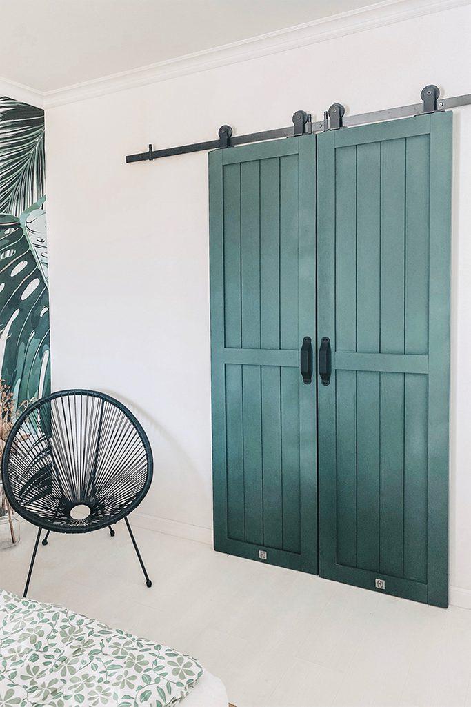 grüne Türen, Kleiderschrank Tür, Schiebetür, schwarzes Schiebetürsystem, schwarzer durchbrochener Sessel, Massivholztür, weiß und grün im Schlafzimmer
