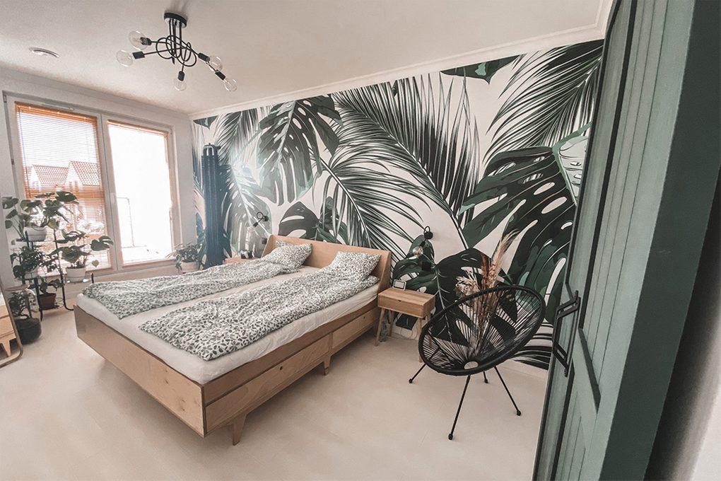 grüne Türen, helles Holz im Schlafzimmer, helles Holz und Grün, Grün im Schlafzimmer, Pflanzenmotiv im Schlafzimmer, botanische Tapete, dekorative Tapete im Schlafzimmer, Leinen mit Blumenmotiv, Pflanze im Schlafzimmer, industrieller Kronleuchter im Schlafzimmer , schwarzer durchbrochener Sessel, helles Holzbett, kleine Nachttisch aus hellem Holz