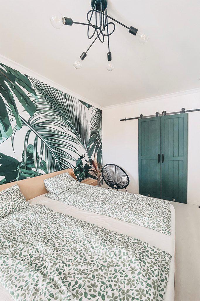grüne Türen, Schlafzimmer mit begehbarem Kleiderschrank, Schiebetür zum Kleiderschrank, Schiebetür im Schlafzimmer, Grün im Schlafzimmer, industrieller Kronleuchter im Schlafzimmer, dekorative Tapete mit Pflanzen, botanische Tapete, grüne Tapete für das Schlafzimmer, durchbrochener Sessel, Pflanzenmotiv auf Bettwäsche, grünes Schlafzimmer