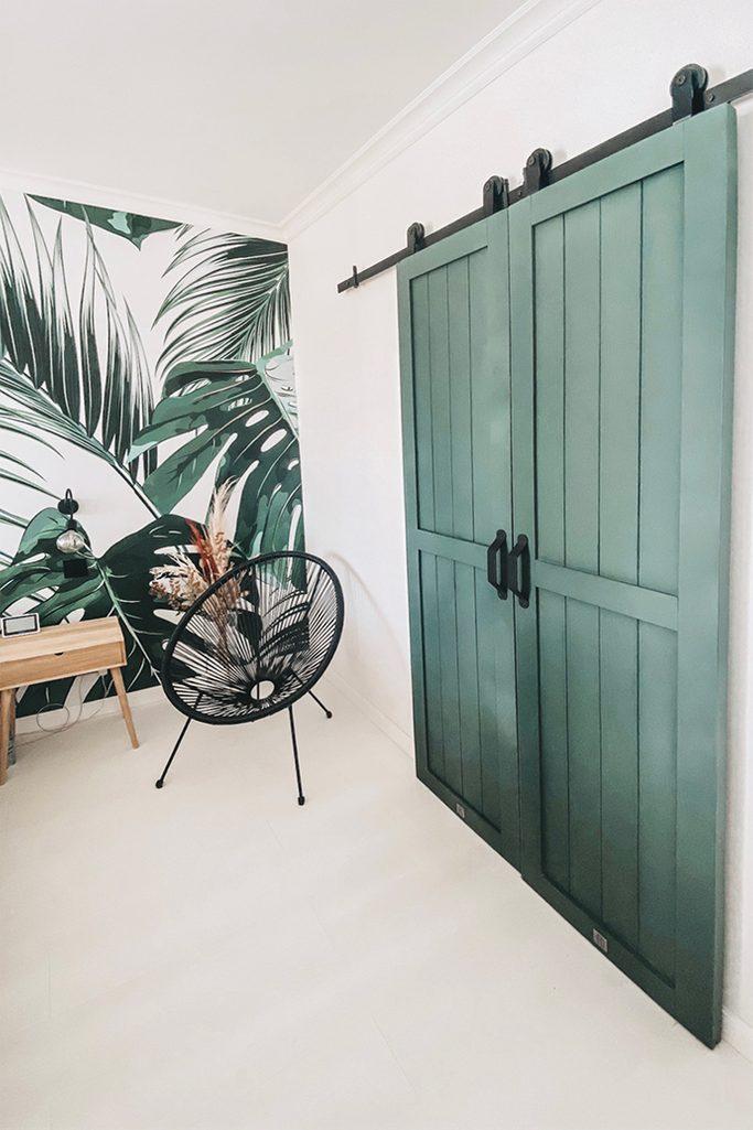 grüne Türen, Schranktür, grüne Schiebetür, Tür aus massivem Holz, dekorative Pflanzentapete, grüne Schlafzimmertapete, schwarzer durchbrochener Sessel, heller Nachttisch aus Holz