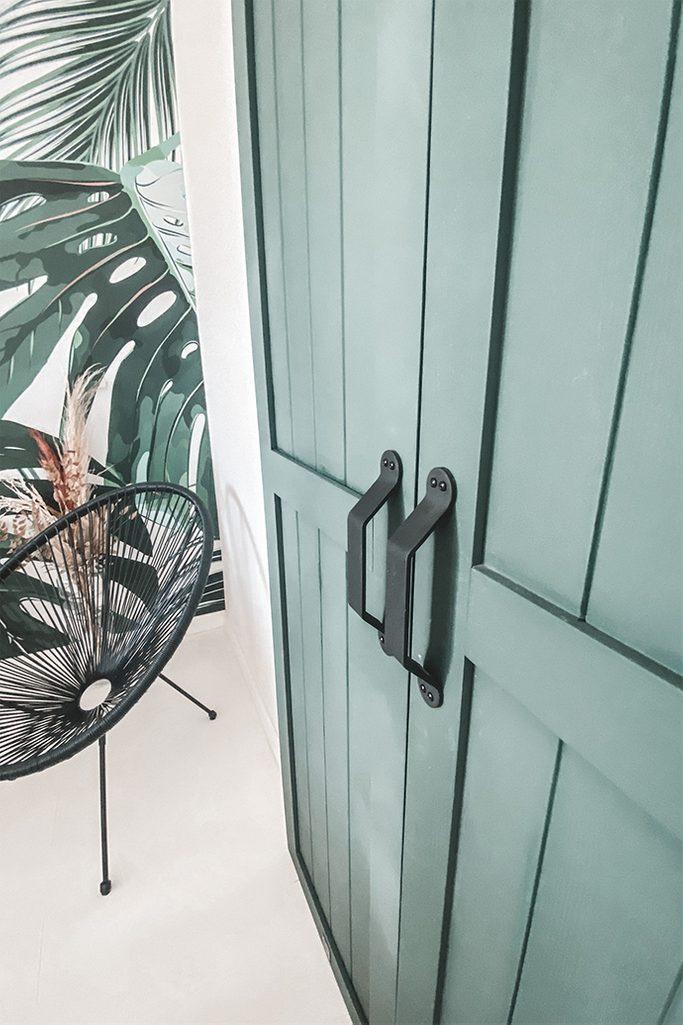 grüne Türen, Schranktür, durchbrochener Sessel, Pflanzentapete, Schiebetürgriffe, schmale Schiebetür