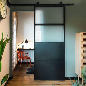 Industrielle Schiebetüren, Metall- und Glas Türen, mit Milchglas gefüllte Türen, Schiebetüren zum Schlafzimmer, kleine Arbeitsecke, roter Stuhl