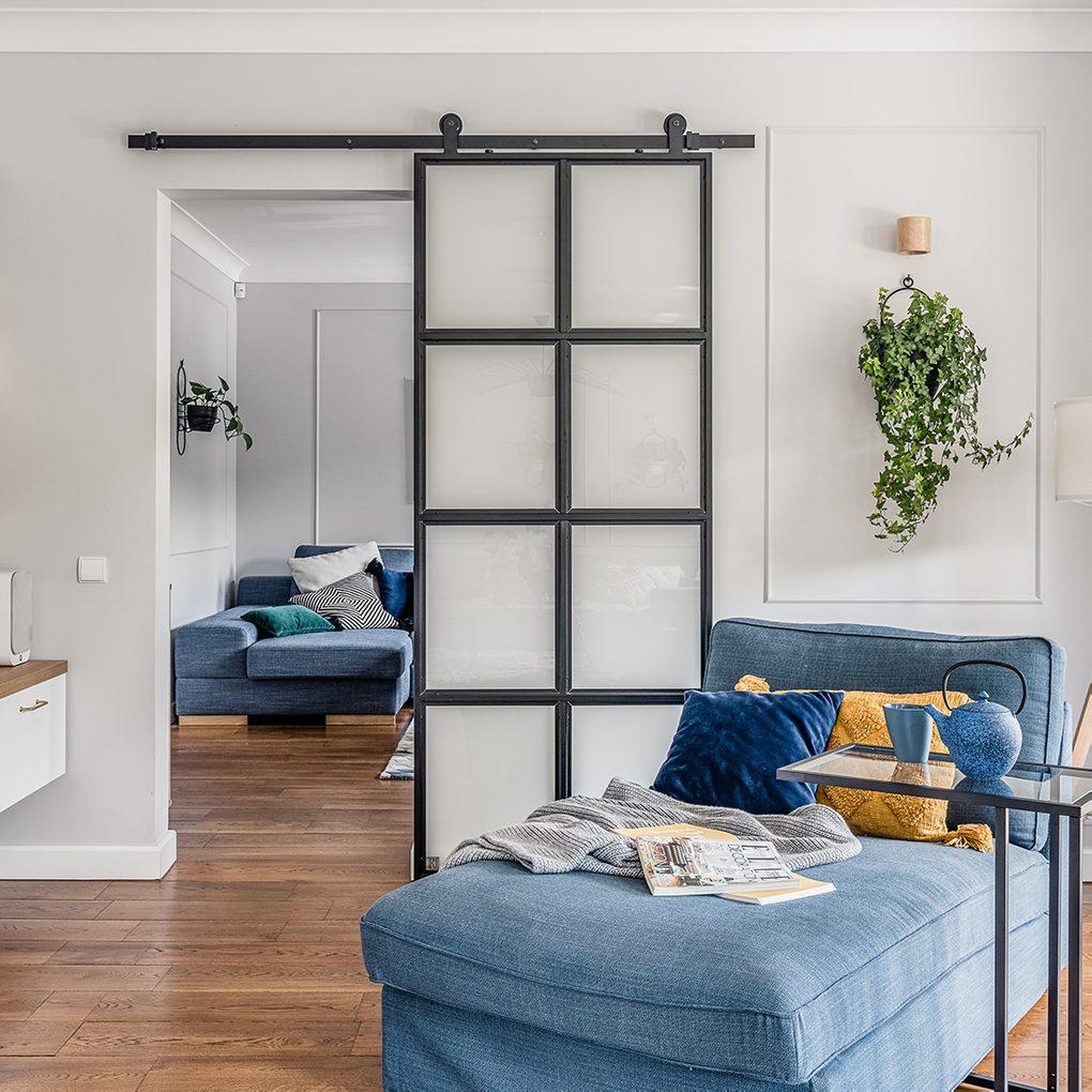 Leseecke, blaues Denim Sofa, Metall- und Glasschiebetür, Industrietür, heller Raum, blaue und gelbe dekorative Kissen, Wandblumenbeet