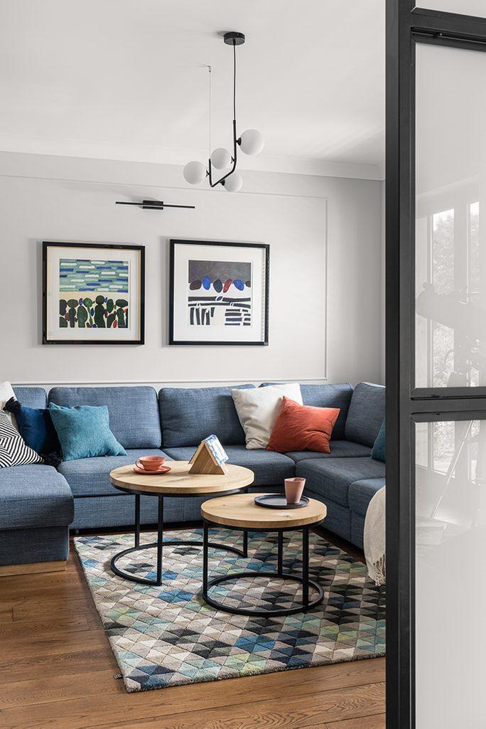 großes Sofa aus blauem Denim, ein Set runder Couchtische, Tische aus hellem Holz und Metall, Holzboden im Wohnzimmer, bunte Kissen auf dem Sofa, abstrakte Gemälde in schwarzen Rahmen, Metalllampe im Wohnzimmer, Teppich im Sitzbereich im Wohnzimmer