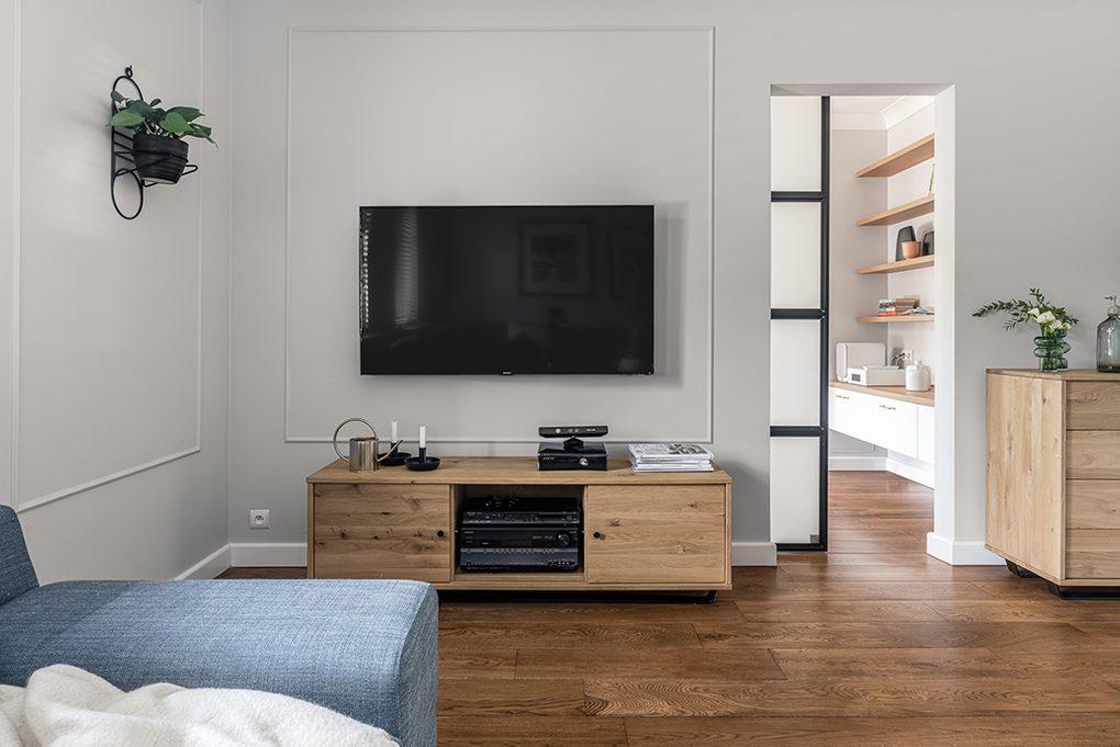 TV-Ecke im Wohnzimmer, TV-Schrank aus hellem Holz, blaues Denim Sofa, Eingang zum großen Wohnzimmer mit Schiebetüren, Holzboden im Wohnzimmer, helle Holzmöbel