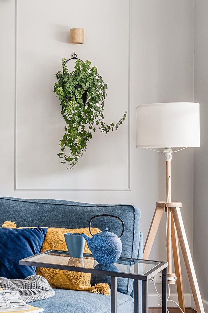metall Blumenbeet an der Wand, blaues Sofa, gelbes Kissen auf dem Sofa, große hölzerne Stehlampe, blaue Teekanne, Beistelltisch aus Metall und Glas, grüne Pflanzen an einer hellen Wand
