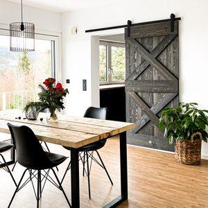 Holz und Metall im Esszimmer, Holzschiebetür, Esstisch aus Holz und Metall, große grüne Pflanze im Korb, schwarze Stühle auf Metallbeinen, Tisch und Stühle im Esszimmer, Tür zur Küche