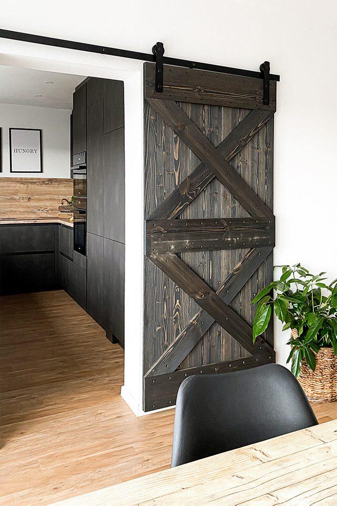 Holz und Metall im Esszimmer, dunkle Möbel in der Küche, Holzschiebetür, schwarzes Schiebesystem, Schiebetür öffnet sich zur Küche, dunkelbraune Einbauküche