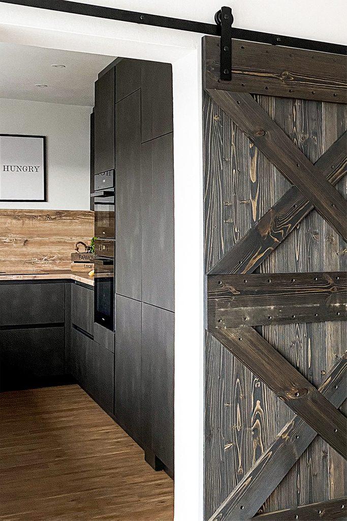 Holz und Metall im Esszimmer, dunkelbraune Einbauküche, dunkle Möbel in der Küche, Holzschiebetür, Schiebesystem, Holztür zur Küche