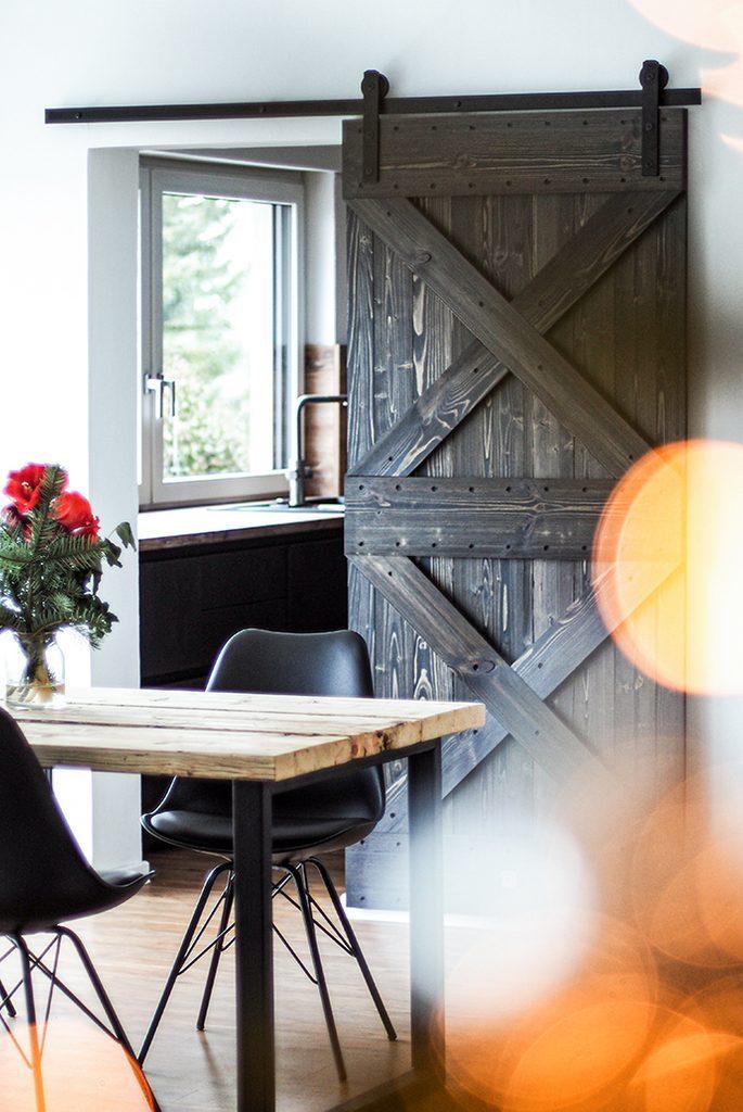 Holz und Metall im Esszimmer, dunkle Holztür, Holzschiebetür zur Küche, Schiebesystem, Esstisch aus Holz und Metall, schwarze Stühle