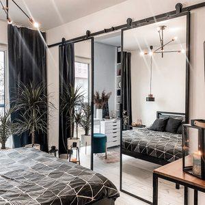 Doppel Schiebetür mit Spiegel, Industrielampe, schwarzem Zubehör im Schlafzimmer, begehbarem Kleiderschrank, modernem Schlafzimmer, Metallbettrahmen, Metallaufhängelampe