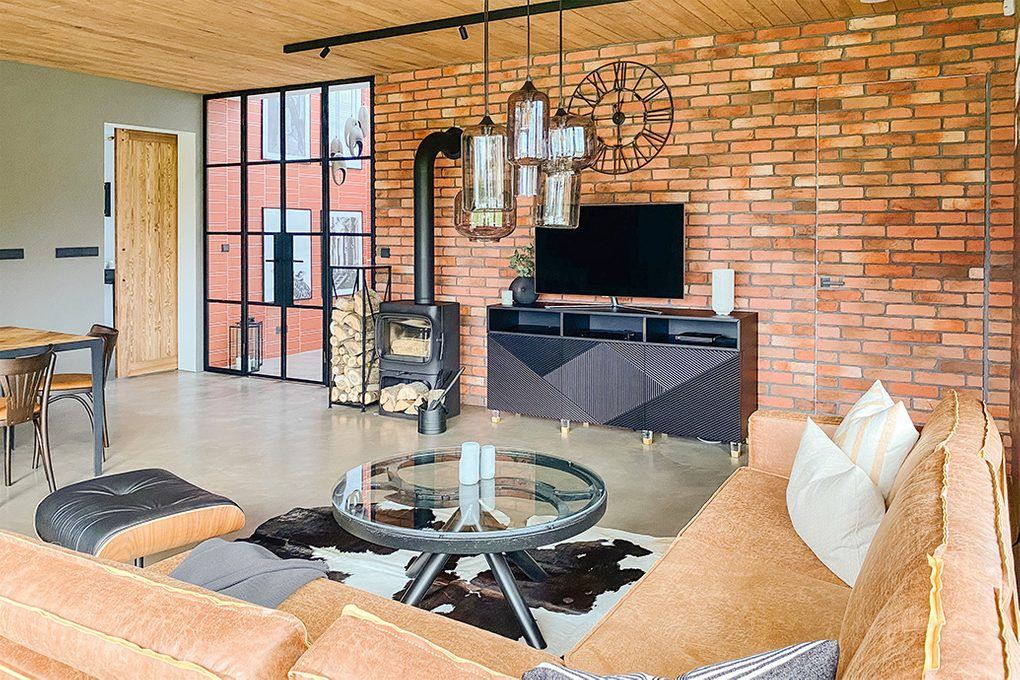 Wohnzimmer im Industrie loft stil, Mikrozement Boden, Holzdecke, schwarze Metallelemente, schwarzer Kamin im Wohnzimmer, Glas- und Stahllampe, Couchtisch aus Glas, Backsteinmauer im Wohnzimmer