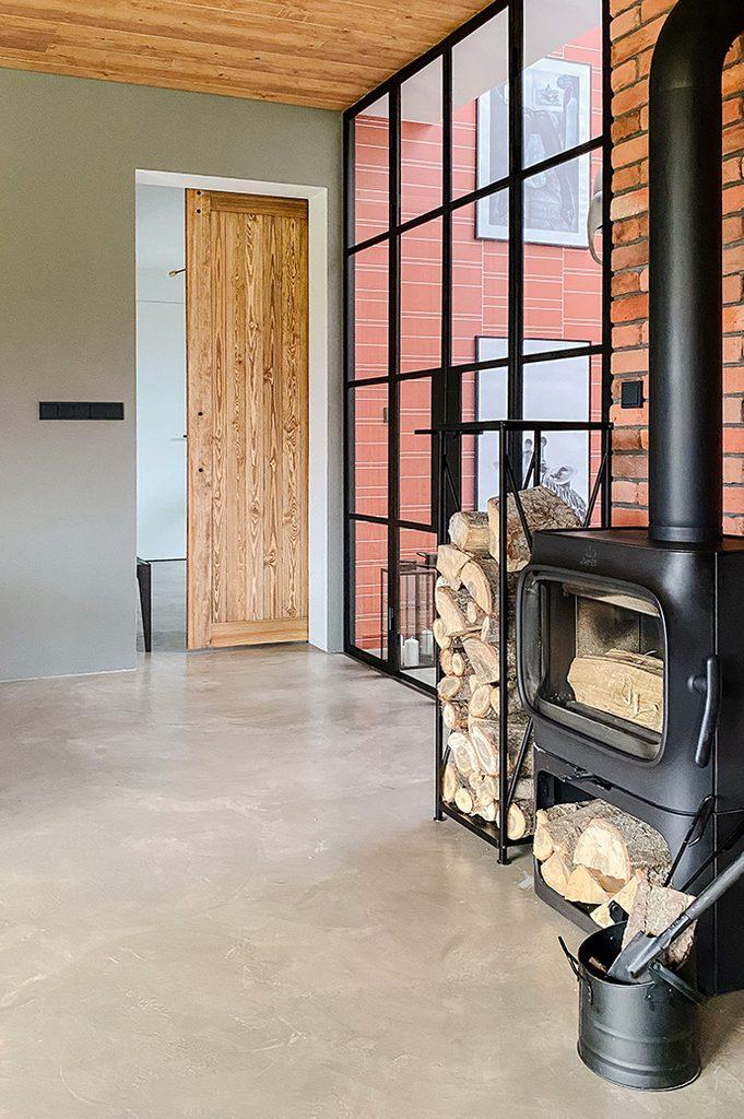 Spiegeltür im Vorraum, schwarzer Metall Kamin im Loft Stil, Glaswand, Mikrozement Boden