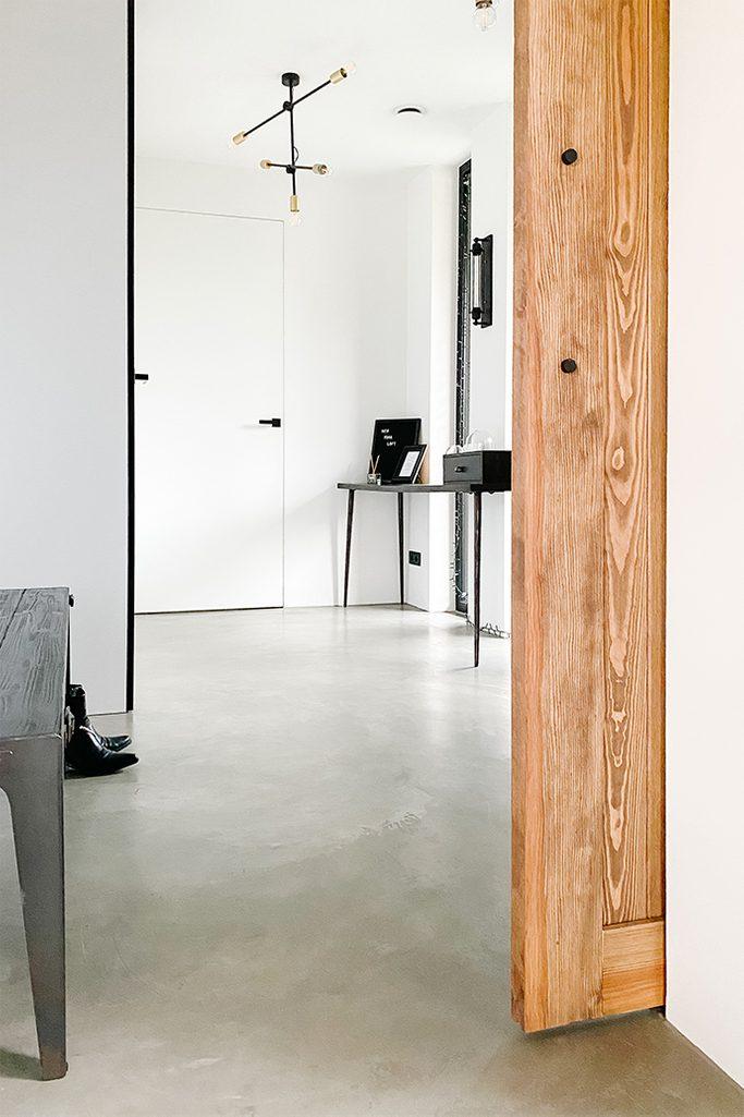 Spiegeltür im Vorraum, Holztür, Mikrozement Boden, schwarzer minimalistischer Tisch im Foyer, weißes und schwarzes Vorraum