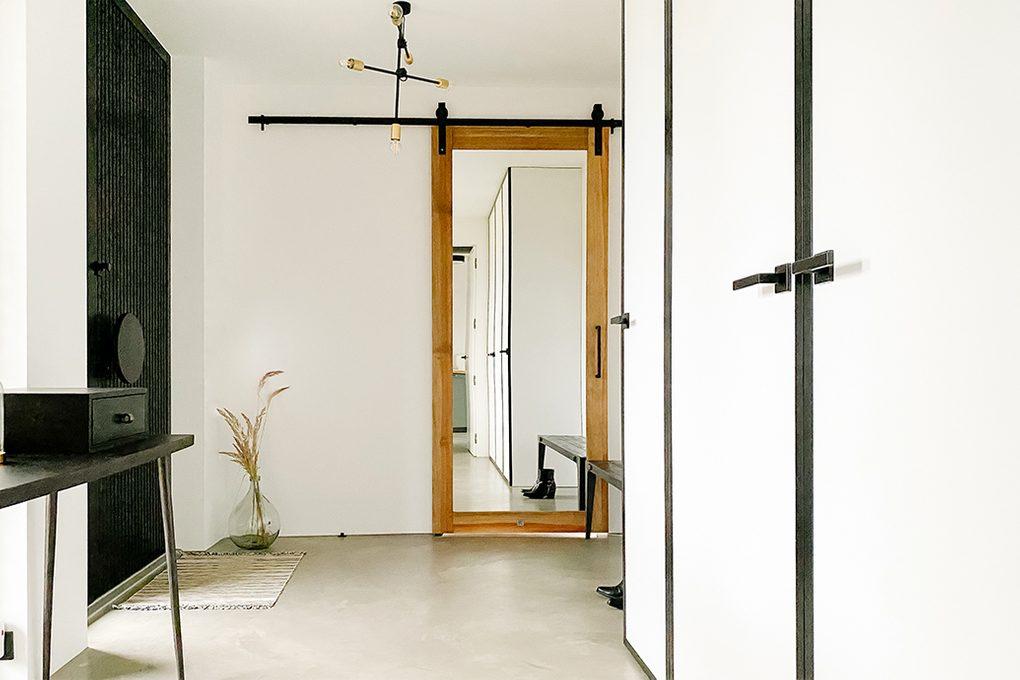 Spiegeltür im Vorraum, großer Spiegel im Foyer, Schiebespiegel im Holzrahmen, schwarz-weißer Vorraum, schwarz-weißer minimalistischer Raum, Mikrozement Boden