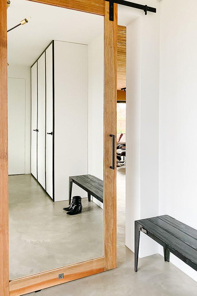 Spiegeltür im Vorraum, großer Spiegel im Holzrahmen, Schiebespiegel, weiße Wände im Vorraum, schwarze minimalistische Bank im Vorraum, Mikrozement Boden