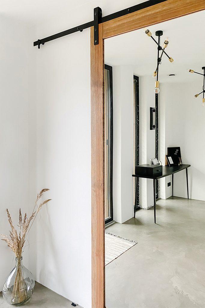 Spiegeltür im Vorraum, schwarzer minimalistischer Tisch im Vorraum, industrielle Hängelampe, Spiegel im Holzrahmen, Glasvase auf dem Boden