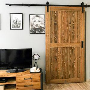 Schiebetüren in einer kleinen Wohnung, Holztür auf schwarzem Schiebesystem installiert, schwarz-weiße Plakate an der Wand, Fernsehschrank aus Stahl und Holz, schwarze dekorative stehende Uhr