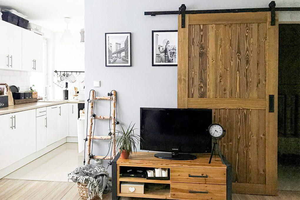 Schiebetüren in einer kleinen Wohnung, weiße Küche mit hölzernen und schwarzen Accessoires, Holztür auf schwarzem Schiebesystem, Fernsehschrank aus Metall und Holz, schwarz-weiße Plakate an der Wand, dekorative Elemente aus Metall und Holz im Wohnzimmer