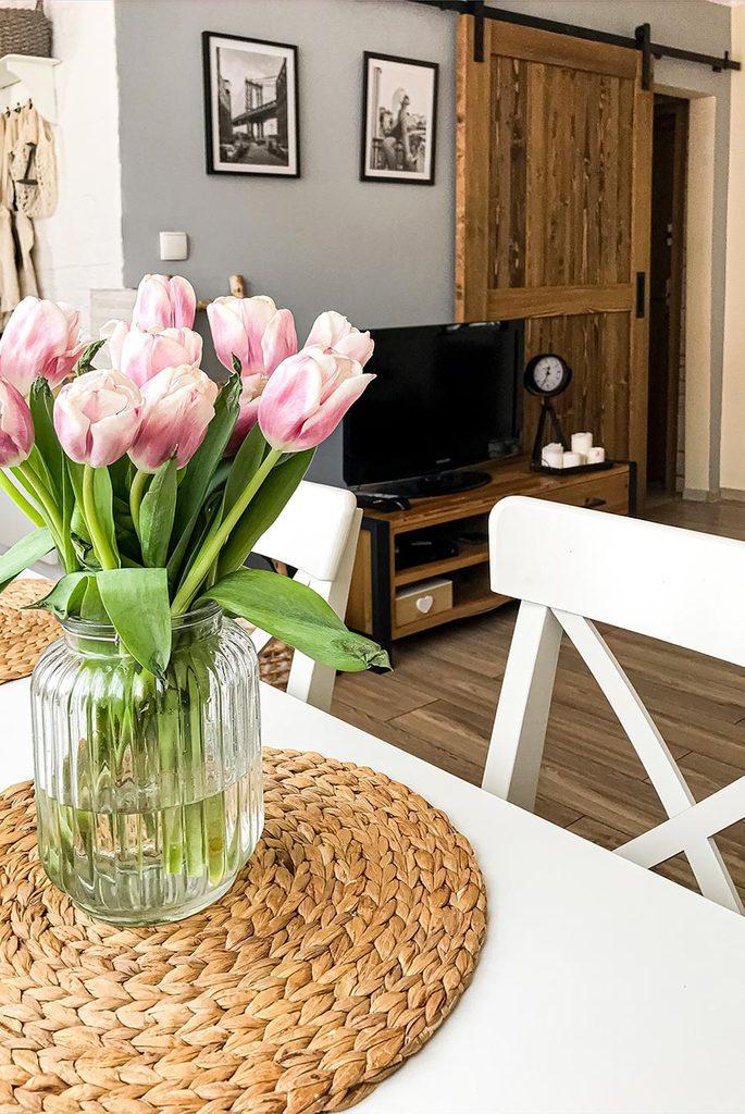 Schiebetüren in einer kleinen Wohnung, Tulpen auf weißem Esstisch in kleinem Wohnzimmer, Schiebetür in kleiner Wohnung, weißer Esstisch und Stühle