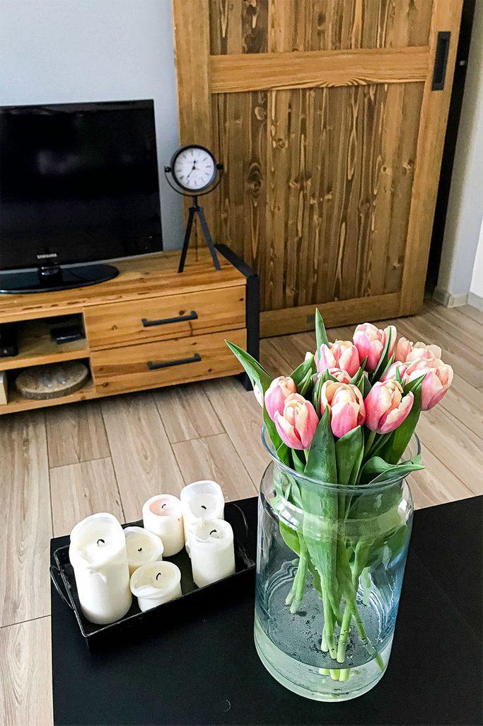 Schiebetüren in einer kleinen Wohnung, Holzschiebetür mit schwarzem Griff, Holz Fernsehschrank, dekorative Metall Uhr auf Holzschrank