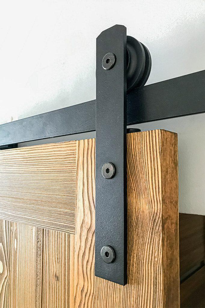 schwarzes Schiebesystem an Holztür montiert