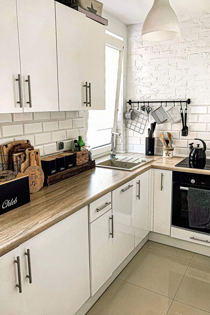 Schiebetüren in einer kleinen Wohnung, weißer Küchenschrank mit Holzplatte, schwarzes Küchenzubehör, weiße Fliesen an der Küchenwand