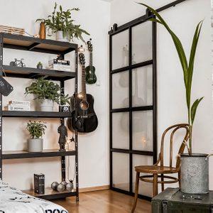 studentenzimmer einrichten, Metall Schiebetür mit Glas, Loft-Stil, Bücherregal-Loft-Stil, Pflanzen im Studentenzimmer, Vintage-Stuhl, weiße Wand und schwarze Dekorationen