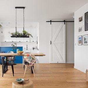 helles Wohnzimmer mit Esstisch und offener Küche, weiße Küche mit Frühstücksbar-Arbeitsplatte in blauer, weißer Schiebetür zum Hauswirtschaftsraum, Fotogalerie an der Wand