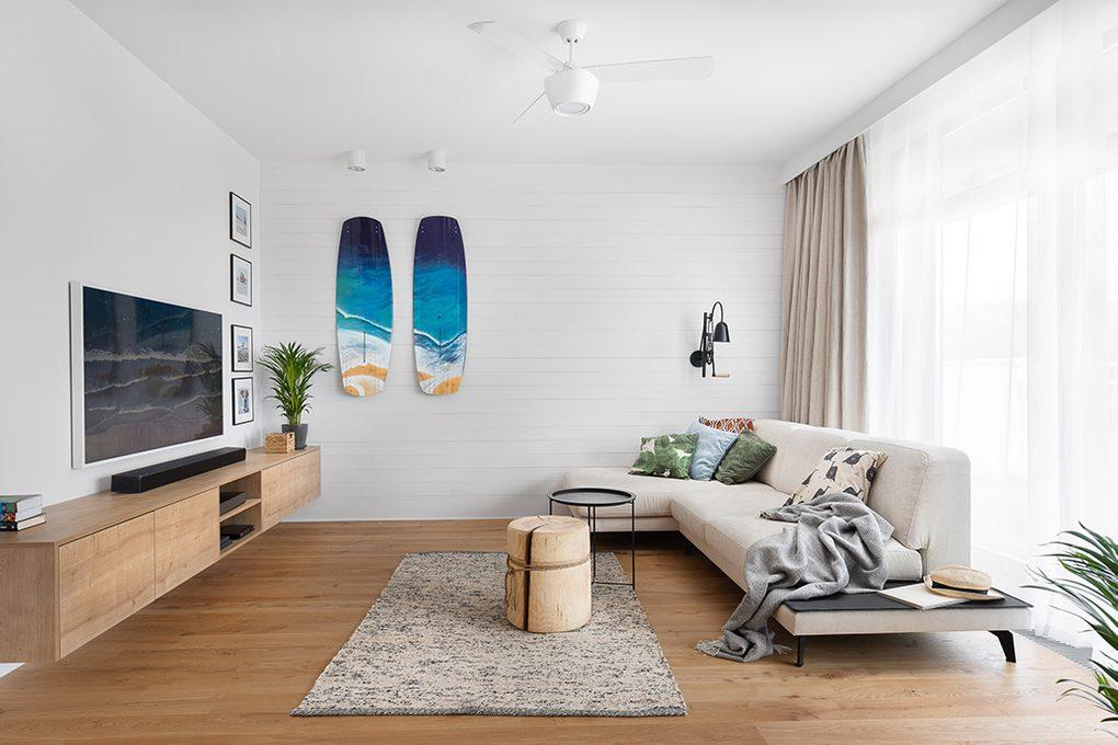 großes und helles Wohnzimmer, weiße Wände im Wohnzimmer, blaues dekoratives Surfbrett an der Wand, hölzerner Couchtisch, großes Sofa