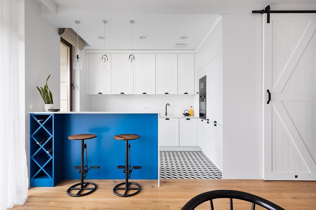 weiße Küche mit schwarzen Accessoires, weiße Schiebetür zum Hauswirtschaftsraum, blaue Akzente in der Küche, industrieller Barhocker mit Fahrrad Pedalen