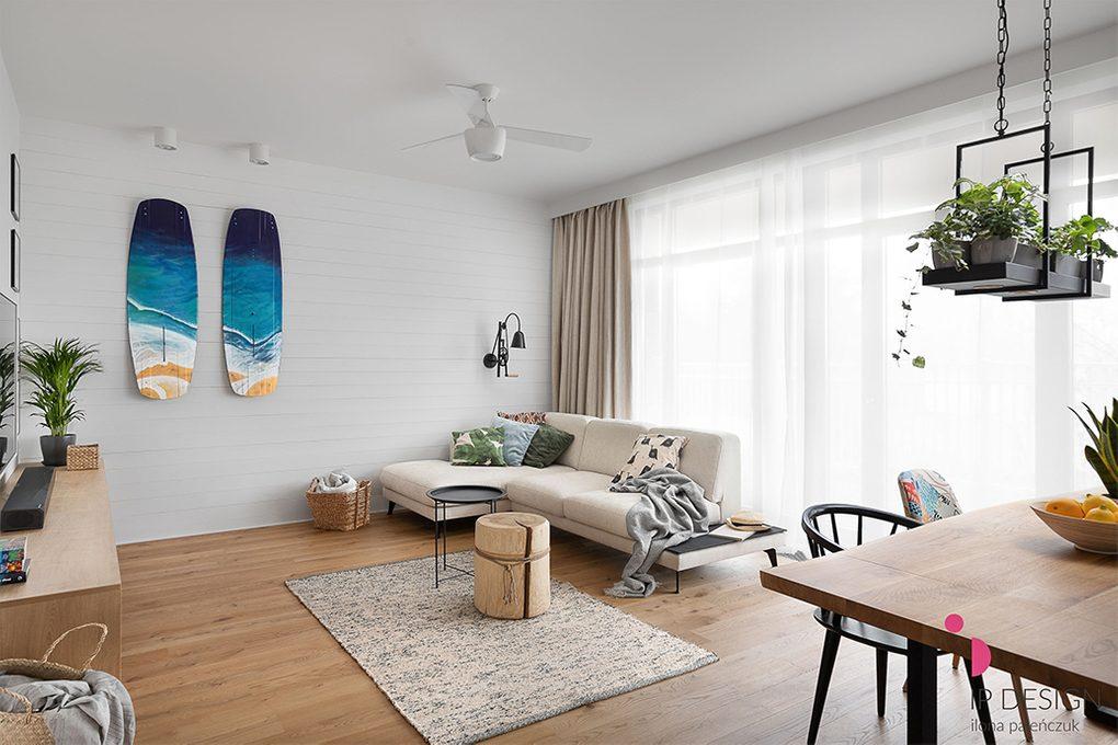 Geräumiges Wohnzimmer im kalifornischen Küstenstil, helles braunes Sofa, Couchtisch aus Holz, blaues dekoratives Surfbrett, weiße Wände im Wohnzimmer mit Holzboden